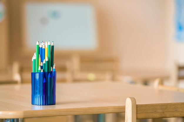 Os lápis coloridos de madeira do desenho arranjaram no jarro plástico no espaço claro da cópia.