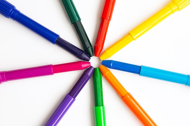 Os lápis de cera coloridos para desenhar têm a forma do sol sobre um fundo branco.
