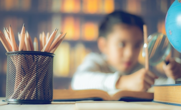 Os lápis em uma tabela de madeira e em uma criança asiática industrioso estão sentando-se em um fundo da mesa.