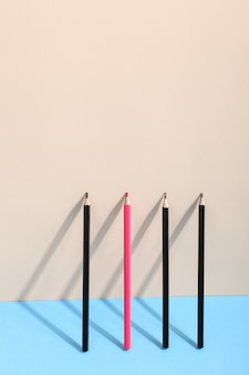 Os lápis estão encostados na parede, projetando uma sombra, desenhando formas geométricas.
