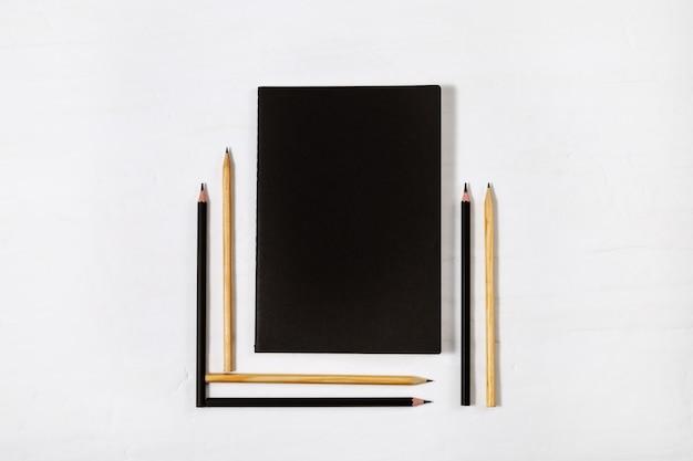 Os lápis geométricos dobraram e fecharam o caderno preto na tabela branca. lápis de madeira pretos e amarelos e livro para desenhar.