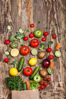 Os legumes de um saco de papel na mesa de madeira