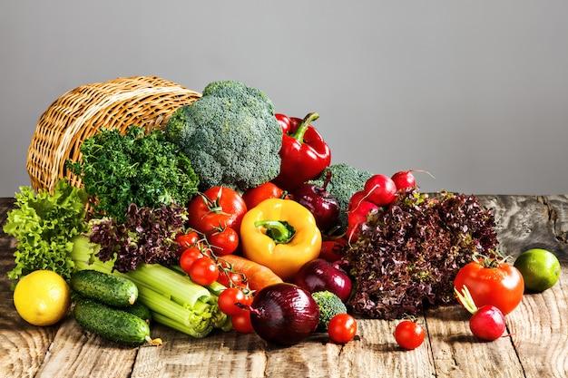 Os legumes de uma cesta na mesa de madeira