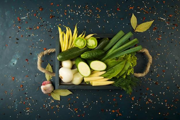Os legumes na caixa na pedra um escuro. jovens ervas cebolas alho feijões verdes amarelo milho especiarias especiais estão em uma caixa de madeira com punhos de corda em uma textura escura.