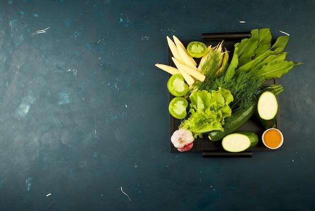Os legumes na caixa na pedra um escuro. jovens verdes cebola alho especiarias brilhantes colocam-se em uma bandeja de madeira com punhos em um texturiz escuro.
