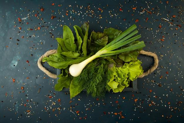 Os legumes na caixa na pedra um escuro. jovens verdes cebola alho especiarias brilhantes estão em uma caixa de madeira com punhos de corda em um texturado escuro.