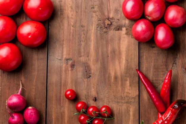 Os legumes vermelhos no fundo da mesa de madeira
