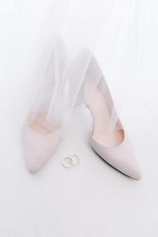 Os lindos sapatos de casamento brancos na noiva