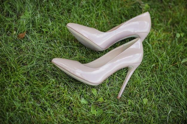 Os lindos sapatos de casamento na grama. sapatos de noiva