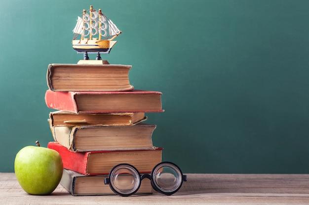 Os livros da velha escola, livros didáticos e material escolar mentem sobre uma mesa de madeira.