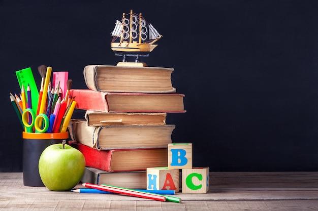 Os livros de texto velhos e as fontes de escola estão na tabela de madeira rústica em um fundo da placa de giz preta.