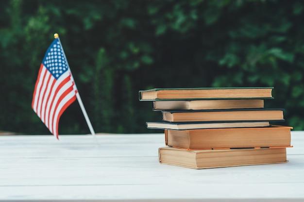 Os livros estão em uma mesa branca, no fundo é uma bandeira americana e folhas verdes.