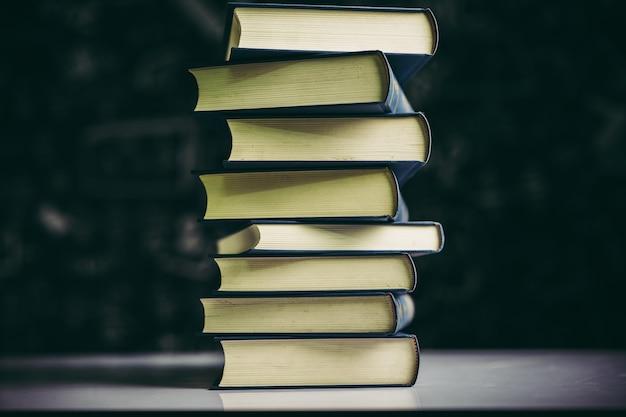 Os livros são colocados em uma pilha de livros sobre a mesa