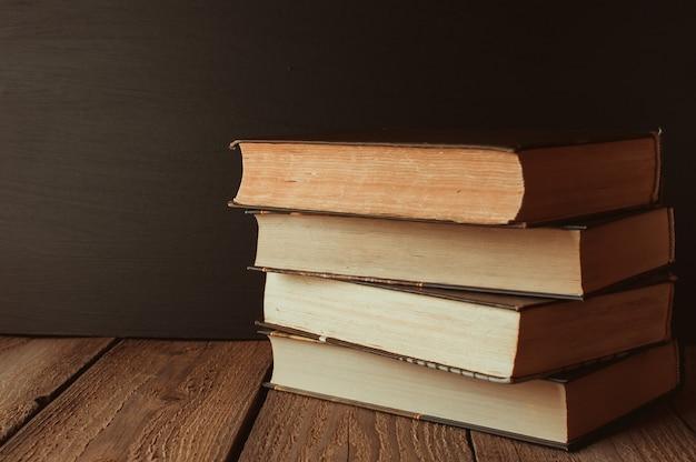 Os livros são empilhados em uma pilha sobre uma mesa de madeira em um fundo de quadro negro.