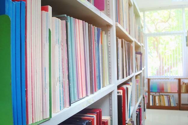 Os livros velhos em estantes com fundo desfocado na biblioteca pública.