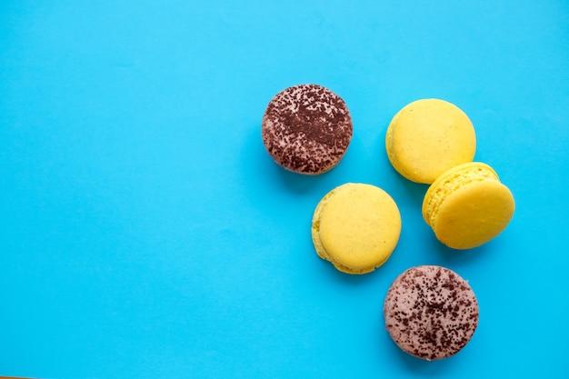 Os macarons coloridos endurecem, configuração do plano da vista superior, bolinho de amêndoa doce no fundo isolado dos doces da cor azul.