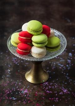 Os macarons coloridos franceses tradicionais em um bolo estão no fundo escuro com espaço da cópia.