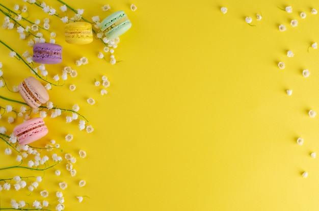 Os macarons ou os bolinhos de amêndoa coloridos decorados com o lírio de florescência do vale florescem no fundo amarelo. conceito de sobremesa doce francês. composição de quadros. lay plana. copyspace
