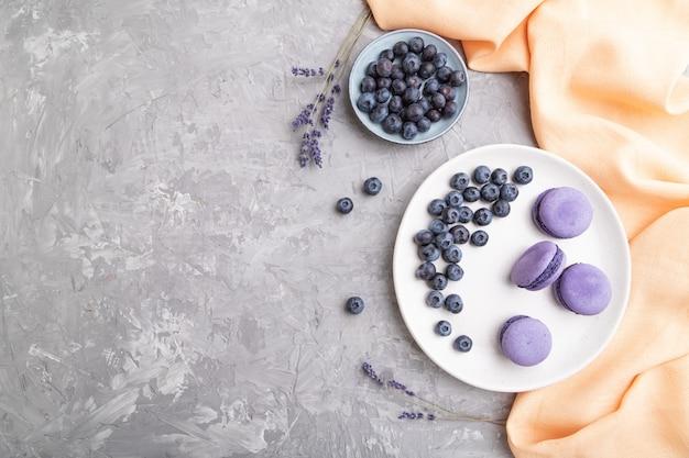 Os macarons ou os bolinhos de amêndoa roxos endurecem com os mirtilos na placa cerâmica branca em um fundo cinzento concreto.