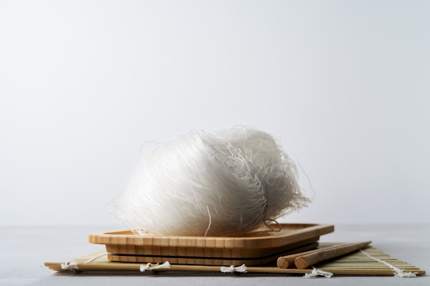 Os macarronetes de arroz finos crus no prato de bambu com os hashis na pedra surgem com espaço da cópia.