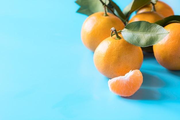 Os mandarino e fatia inteiros frescos com as folhas na tabela azul. alimentação saudável . alimentos à base de plantas.