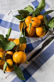 Os mandarino ou fruta madura alaranjada das tangerinas com folhas verdes, sobre o fundo de madeira azul rústico.