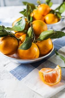 Os mandarino ou fruta madura alaranjada das tangerinas com folhas verdes, sobre o fundo de madeira branco rústico.