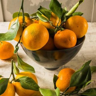 Os mandarino ou fruta madura alaranjada das tangerinas com folhas verdes, sobre o fundo de madeira rústico.