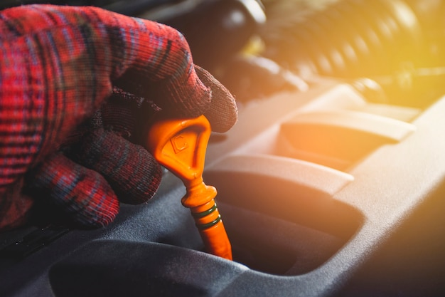 Os mecânicos entregam o medidor de nível de óleo da vareta da vareta com cor alaranjada para verificar o nível de óleo do motor do sistema de motor, conceito de manutenção automotivo.