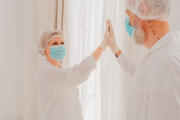 Os médicos com máscara e protetor facial se trocam com as mãos