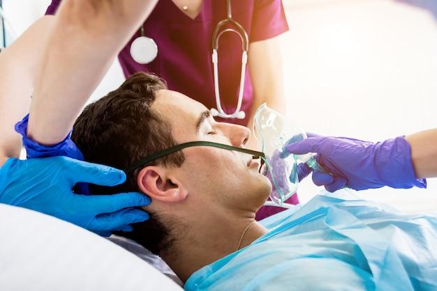 Os médicos dão ressuscitação a um paciente do sexo masculino na sala de emergência. massagem cardíaca