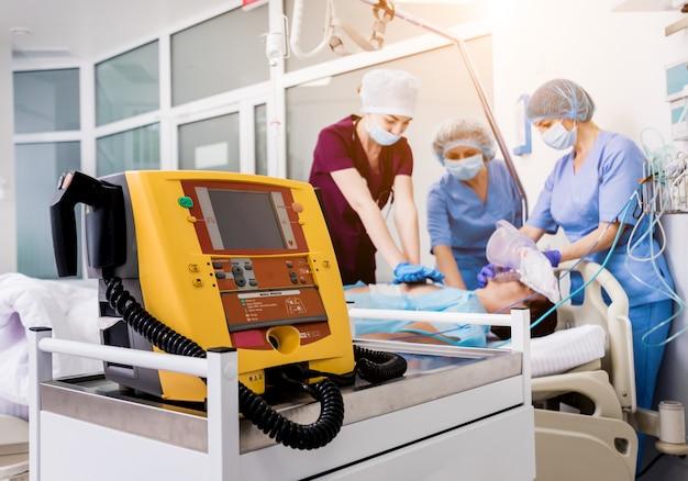 Os médicos dão ressuscitação a um paciente do sexo masculino na sala de emergência.