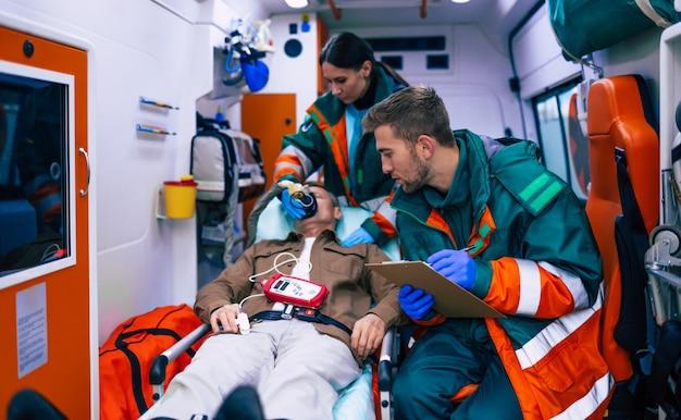 Os médicos de emergência ou paramédicos estão trabalhando com um paciente idoso enquanto ele está deitado em uma maca em uma ambulância.