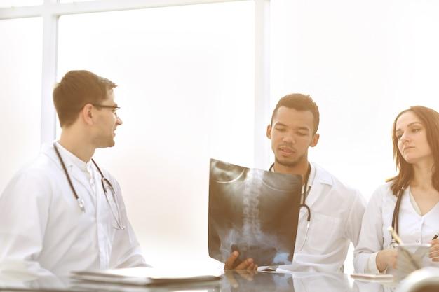 Os médicos discutem a radiografia do paciente sentado à mesa. o conceito de saúde