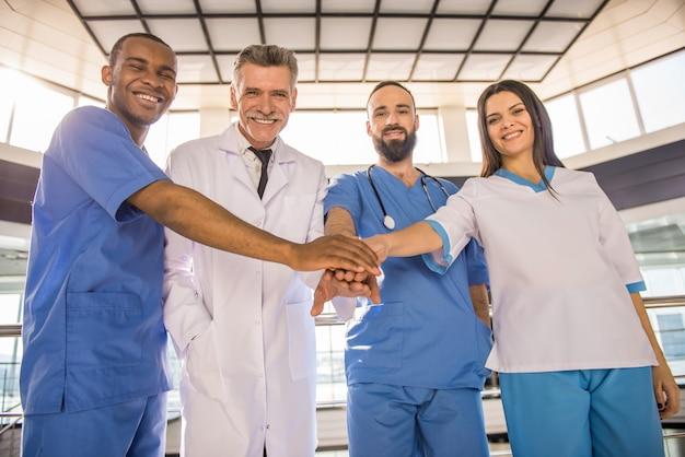 Os médicos do hospital juntaram as mãos como uma equipe.