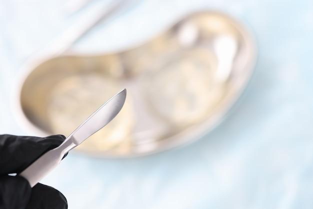 Os médicos entregam uma luva de borracha segurando o bisturi sobre o close up dos implantes mamários. cirurgia plástica