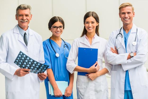 Os médicos estão de pé e sorrindo.