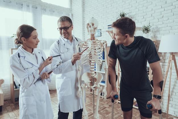 Os médicos estão mostrando o esqueleto para o atleta lesionado