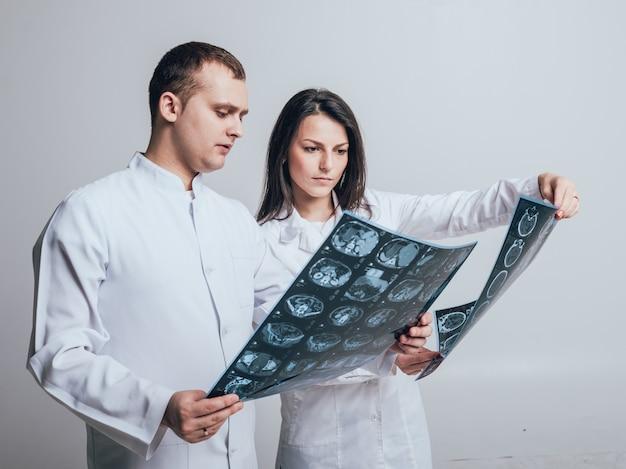 Os médicos examinam atentamente a ressonância magnética do paciente.