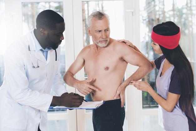 Os médicos examinam um homem idoso que tem dor nas costas nas costas.