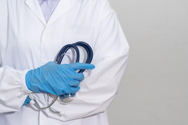 Os médicos usam uniformes e luvas azuis segurando um estetoscópio de perto