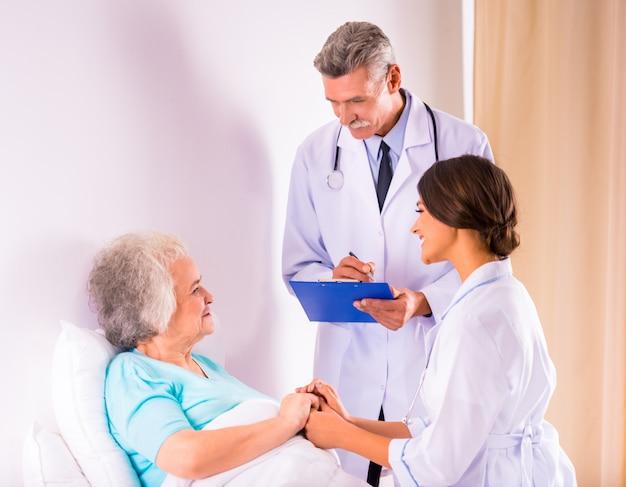 Os médicos vieram para ver uma velha em uma clínica.