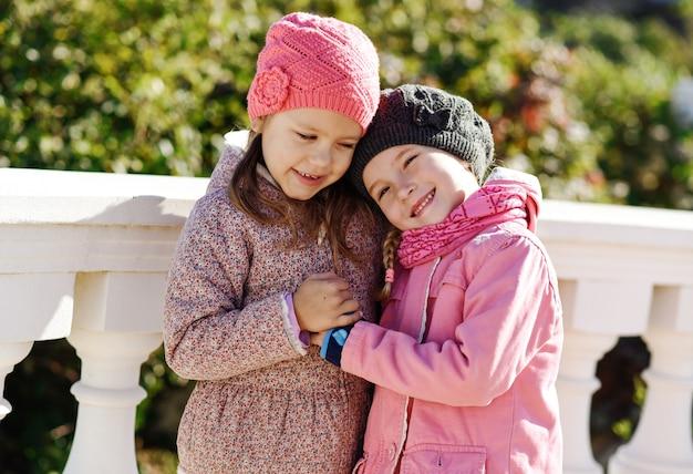 Os melhores amigos estão se abraçando ao ar livre e sorrindo
