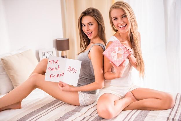 Os melhores amigos estão se divertindo com presentes e cartão postal.