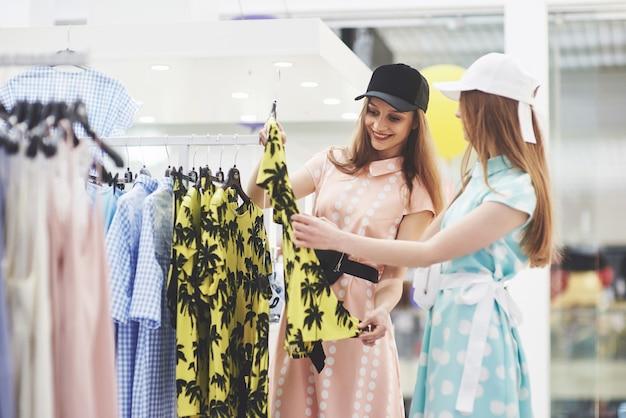 Os melhores amigos passam o tempo juntos. duas lindas garotas fazem compras na loja de roupas. eles se vestiam com as mesmas roupas.