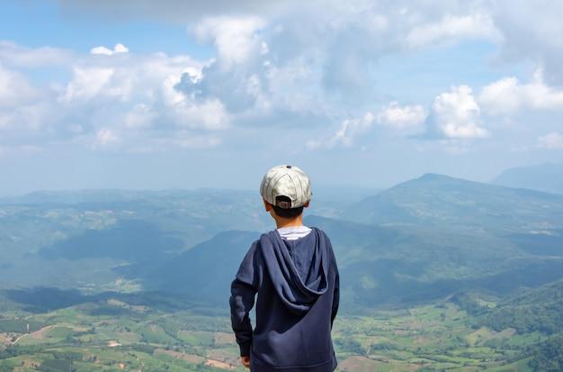 Os meninos asiáticos vêem as montanhas e o céu no parque nacional de phu rua em loei.