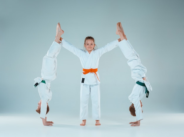 Os meninos e meninas adolescentes lutando no treinamento de aikido na escola de artes marciais. estilo de vida saudável e conceito de esportes. adolescentes em quimono branco sobre fundo branco. crianças com rostos concentrados