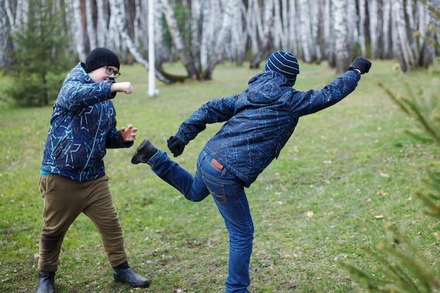Os meninos estão brincando no gramado verde. um adolescente de chapéu preto e óculos está lutando com o amigo na grama verde.