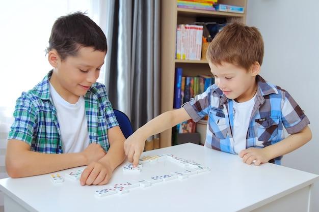 Os meninos jogam dominó em casa na mesa. o conceito de lazer no isolamento de quarentena. o irmão mais velho ensina o irmão mais novo a jogar dominó.