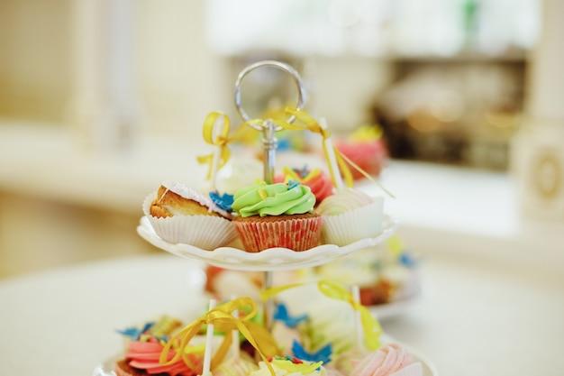 Os mini queques cobriram com os mini anéis de espuma cor-de-rosa em uma tabela da sobremesa.